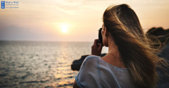 Woman taking picture of sun setting over sea